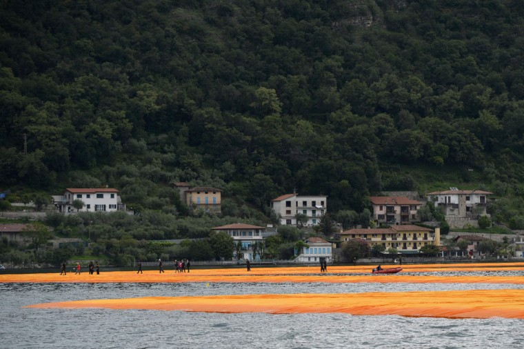 """A picture shows the monumental installation """"The Floating Piers"""" created by Artist Christo Vladimirov Javacheff and Jeanne-Claude, on June 16, 2016 during a press preview at the lake Iseo, northern Italy. (FILIPPO MONTEFORTE/AFP/Getty Images)"""
