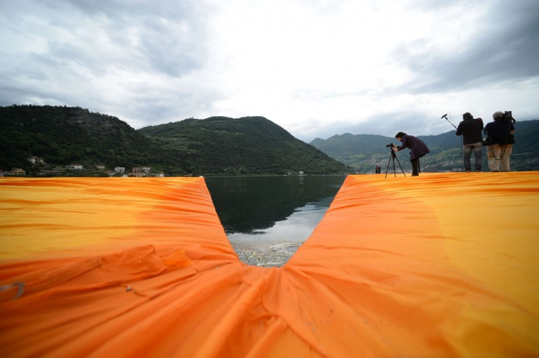 """People take pictures of the monumental installation """"The Floating Piers"""" created by Artist Christo Vladimirov Javacheff and Jeanne-Claude, on June 16, 2016 during a press preview at the lake Iseo, northern Italy. (FILIPPO MONTEFORTE/AFP/Getty Images)"""