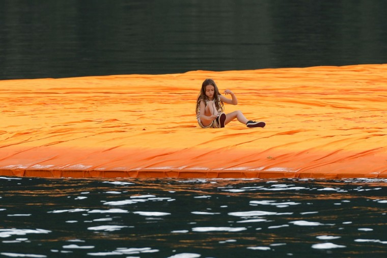 """A girl laces her shoes as she sits on the monumental installation """"The Floating Piers"""" created by Artist Christo Vladimirov Javacheff and Jeanne-Claude, on June 16, 2016 during a press preview at the lake Iseo, northern Italy. (FILIPPO MONTEFORTE/AFP/Getty Images)"""