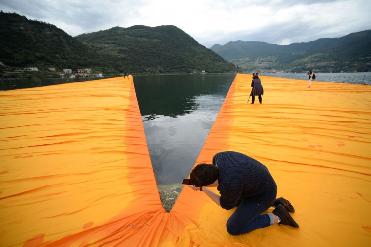 """A man takes pictures of the monumental installation """"The Floating Piers"""" created by Artist Christo Vladimirov Javacheff and Jeanne-Claude, on June 16, 2016 during a press preview at the lake Iseo, northern Italy. (FILIPPO MONTEFORTE/AFP/Getty Images)"""