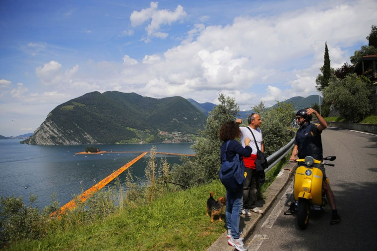 Tourists speak to a man on a scooter as the monumental installation entitled 'The Floating Piers' created by artist Christo Vladimirov Javacheff can be seen below on Iseo Lake, in northern Italy, on June 18, 2016. (MARCO BERTORELLO/AFP/Getty Images)