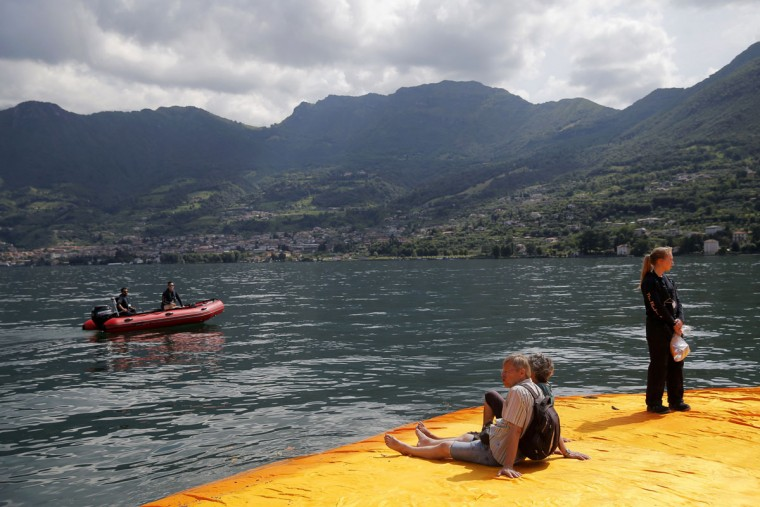 People sit on the monumental installation entitled 'The Floating Piers' created by artist Christo Vladimirov Javacheff on Iseo Lake, in northern Italy, on June 18, 2016. (MARCO BERTORELLO/AFP/Getty Images)