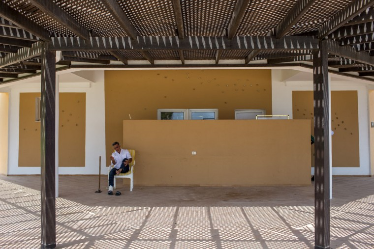 A hotel employee cleans sand from his feet at the closed Imperial Marhaba Hotel on June 24, 2016 in Sousse, Tunisia. The Imperial Marhaba hotel was the main target of the 2015 Sousse beach terrorist attack that killed 38 people including 30 Britons. The hotel attempted to stay open for three months after the attacks, however low occupancy forced the hotel to close. Since then it has operated with a skeleton staff, who work to maintain the rooms and grounds, other permanent hotel staff were able to be placed in temporary jobs at two other hotels owned by the same chain. The hotel hopes to open again by next spring or as soon as British travel advisories and restrictions are lifted for Tunisia. Before the 2011 revolution, tourism in Tunisia accounted for approximately 7% of the countries GDP. The two 2015 terrorist attacks at the Bardo Museum and Sousse Beach saw tourism numbers plummet even further forcing hotels to close and many tourism and hospitality workers to lose their jobs. The 26th of June 2016 marks the anniversary of the Sousse beach attacks. (Photo by Chris McGrath/Getty Images)