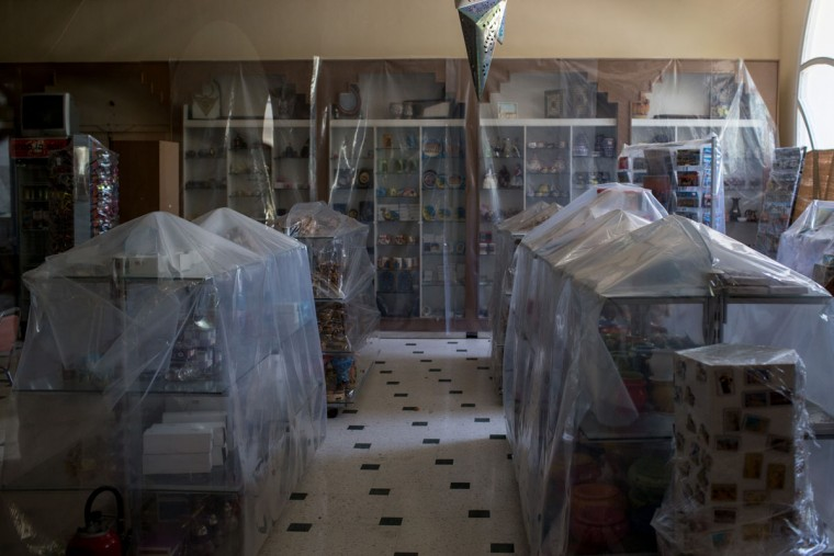 Plastic sheeting is seen covering souvenirs at the gift shop at the closed Imperial Marhaba Hotel on June 24, 2016 in Sousse, Tunisia. The Imperial Marhaba hotel was the main target of the 2015 Sousse beach terrorist attack that killed 38 people including 30 Britons. The hotel attempted to stay open for three months after the attacks, however low occupancy forced the hotel to close. Since then it has operated with a skeleton staff, who work to maintain the rooms and grounds, other permanent hotel staff were able to be placed in temporary jobs at two other hotels owned by the same chain. The hotel hopes to open again by next spring or as soon as British travel advisories and restrictions are lifted for Tunisia. Before the 2011 revolution, tourism in Tunisia accounted for approximately 7% of the countries GDP. The two 2015 terrorist attacks at the Bardo Museum and Sousse Beach saw tourism numbers plummet even further forcing hotels to close and many tourism and hospitality workers to lose their jobs. The 26th of June 2016 marks the anniversary of the Sousse beach attacks. (Photo by Chris McGrath/Getty Images)