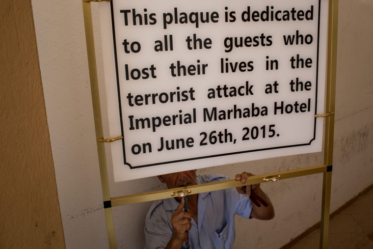 A hotel employee fixes a memoriam sign in preparation for the anniversary of the Sousse Beach attack at the closed Imperial Marhaba Hotel on June 24, 2016 in Sousse, Tunisia. The Imperial Marhaba hotel was the main target of the 2015 Sousse beach terrorist attack that killed 38 people including 30 Britons. The hotel attempted to stay open for three months after the attacks, however low occupancy forced the hotel to close. Since then it has operated with a skeleton staff, who work to maintain the rooms and grounds, other permanent hotel staff were able to be placed in temporary jobs at two other hotels owned by the same chain. The hotel hopes to open again by next spring or as soon as British travel advisories and restrictions are lifted for Tunisia. Before the 2011 revolution, tourism in Tunisia accounted for approximately 7% of the countries GDP. The two 2015 terrorist attacks at the Bardo Museum and Sousse Beach saw tourism numbers plummet even further forcing hotels to close and many tourism and hospitality workers to lose their jobs. The 26th of June 2016 marks the anniversary of the Sousse beach attacks. (Photo by Chris McGrath/Getty Images)