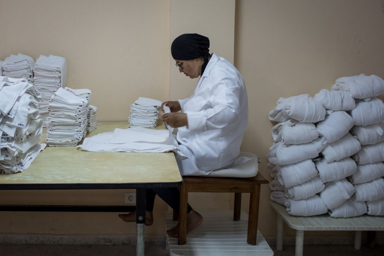 An employee folds napkins in the laundry of the closed Imperial Marhaba Hotel on June 24, 2016 in Sousse, Tunisia. The Imperial Marhaba hotel was the main target of the 2015 Sousse beach terrorist attack that killed 38 people including 30 Britons. The hotel attempted to stay open for three months after the attacks, however low occupancy forced the hotel to close. Since then it has operated with a skeleton staff, who work to maintain the rooms and grounds, other permanent hotel staff were able to be placed in temporary jobs at two other hotels owned by the same chain. The hotel hopes to open again by next spring or as soon as British travel advisories and restrictions are lifted for Tunisia. Before the 2011 revolution, tourism in Tunisia accounted for approximately 7% of the countries GDP. The two 2015 terrorist attacks at the Bardo Museum and Sousse Beach saw tourism numbers plummet even further forcing hotels to close and many tourism and hospitality workers to lose their jobs. The 26th of June 2016 marks the anniversary of the Sousse beach attacks. (Photo by Chris McGrath/Getty Images)