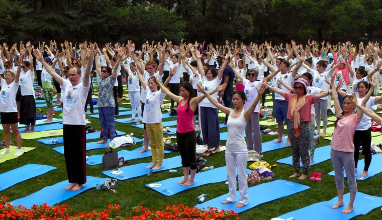SHANGHAI, CHINA - JUNE 21: Nearly 500 yoga enthusiasts perform yoga under the guidance of Indian yoga instructors at Jing'an Park to welcome the International Day of Yoga on June 21, 2016 in Shanghai, China. Proposed by Indian Prime Minister Narendra Modi, the International Day of Yoga is set on June 21 each year. (Photo by VCG/VCG via Getty Images)