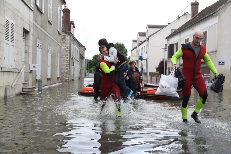 Rescuers evacuate residents accross a flooded street on June 1, 2016 in Souppes-sur-Loing, southeast of Paris. Torrential downpours have lashed parts of northern Europe in recent days, leaving four dead in Germany, breaching the banks of the Seine in Paris and flooding rural roads and villages. (AFP PHOTO / KENZO TRIBOUILLARD)