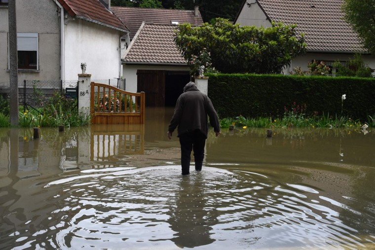A resident walks accross a flooded street on June 1, 2016 in Nemours, southeast of Paris. Torrential downpours have lashed parts of northern Europe in recent days, leaving four dead in Germany, breaching the banks of the Seine in Paris and flooding rural roads and villages. (AFP PHOTO / DOMINIQUE FAGET)