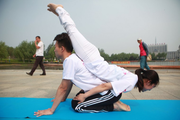 CHANGCHUN, CHINA - JUNE 20: A male yoga instructor practices yoga with partner on June 20, 2016 in Changchun, Jilin Province of China. A yoga instructor of post 90s promotes yoga with other enthusiasts at a Changchun square to welcome the upcoming International Day of Yoga which falls on June 21 each year. (Photo by VCG/VCG via Getty Images)