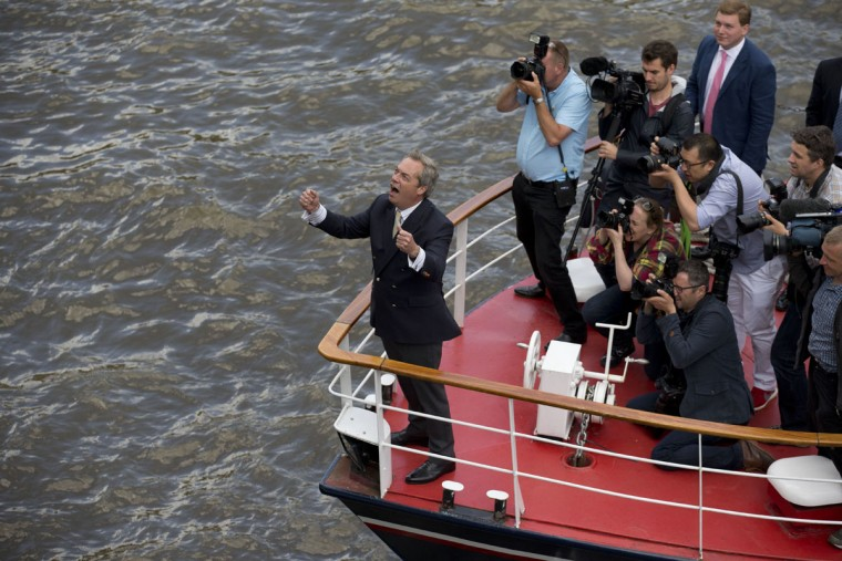 "UK Independence Party leader Nigel Farage reacts to supporters cheering him from Westminster Bridge as he travels on a boat for an EU referendum campaign stunt in which a flotilla of boats supporting ""Leave"" sailed up the River Thames outside the Houses of Parliament in London, Wednesday, June 15, 2016. A flotilla of boats protesting EU fishing polices has sailed up the River Thames to the Houses of Parliament as part of a campaign backing Britain's exit from the European Union. The flotilla was greeted by boats carrying ""remain"" supporters. (AP Photo/Matt Dunham)"