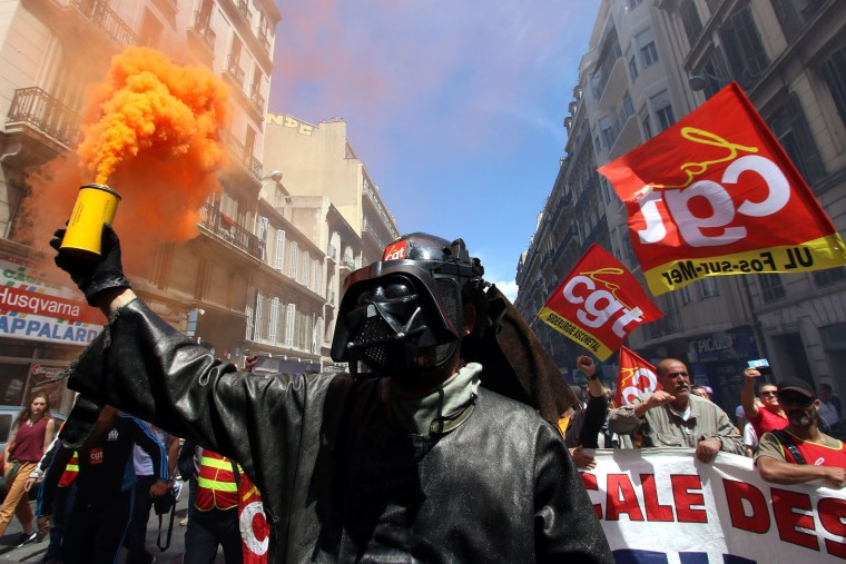 A steelworker from the ArcelorMittal steel plant in Fos-sur-Mer wearing a mask of Darth Vader, burns flares during a demonstration in Marseille, southern France, Thursday, June 2, 2016. Several thousand protestors are demonstrating during a day of strikes and protest against the law job government reform. (AP Photo/Claude Paris)