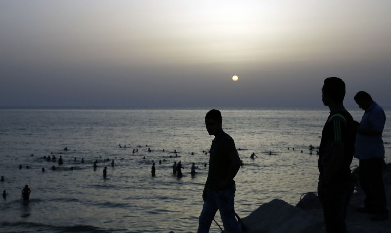Palestinians are silhouetted by the sunset, as others enjoy swimming on the last Friday day before the holy month of Ramadan at the beach of the Mediterranean sea in Gaza City, Friday, June 3, 2016. (AP Photo/Hatem Moussa)
