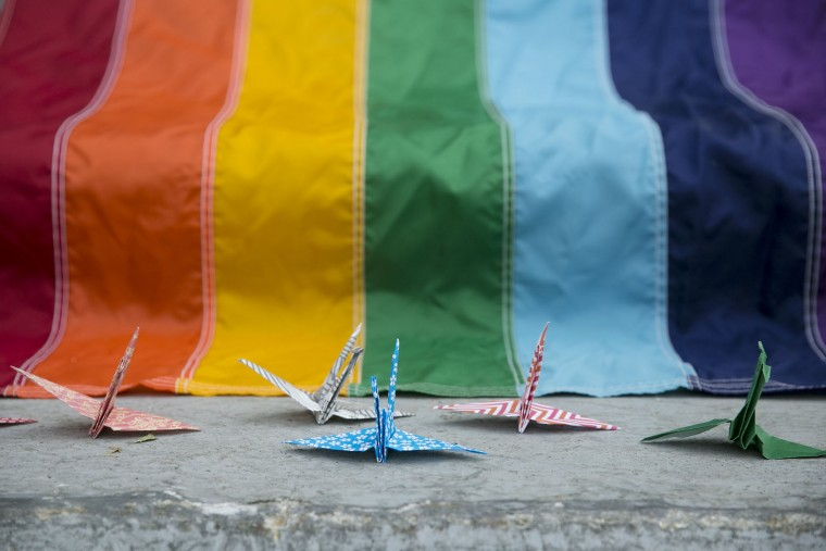 50 origami birds made by Samantha Brouwer and Gabrielle Grace sit around a rainbow flag during a vigil honoring the Orlando shooting victims hosted by the Kalamazoo Gay Lesbian Resource Center in Kalamazoo, Mich. on Monday, June 13, 2016. A gunman has killed dozens of people in a massacre at a crowded gay nightclub in Orlando, Fla. on Sunday, making it the deadliest mass shooting in modern U.S. history. (Chelsea Purgahn/Kalamazoo Gazette-MLive Media Group via AP)