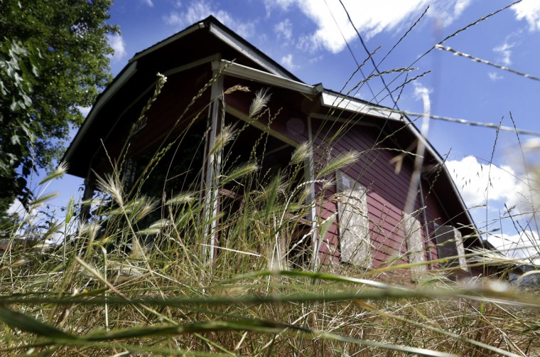 "Dense growth surrounds an abandoned, boarded up house in Portland, Ore., Tuesday, June 14, 2016. City officials in this booming Pacific Northwest metropolis have developed a plan to foreclose on so-called ""zombie homes"" for first time in 50 years as Portland grapples with a swelling population and skyrocketing home costs that threaten to lock new homeowners out of the market. (AP Photo/Don Ryan)"