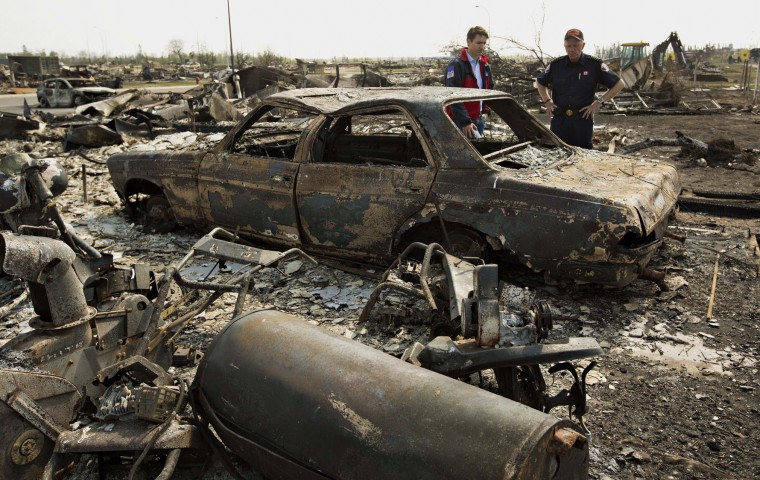FILE -- In this May 13, 2016 file photo, Canadian Prime Minister Justin Trudeau, left, and Fort McMurray Fire Chief Darby Allen look over a burnt out car during a visit to Fort McMurray, Canada. Canada's central bank says the Canadian economy will shrink and become much weaker than expected because of Alberta's devastating wildfires, which shut down its oil sands production. The Bank of Canada, which kept its key interest rate on hold Wednesday, May 25, said its preliminary assessment is that the destruction and halt to oil production will knock about 1 1/4 percentage points off real GDP growth in the second quarter. (Jason Franson/The Canadian Press via AP)