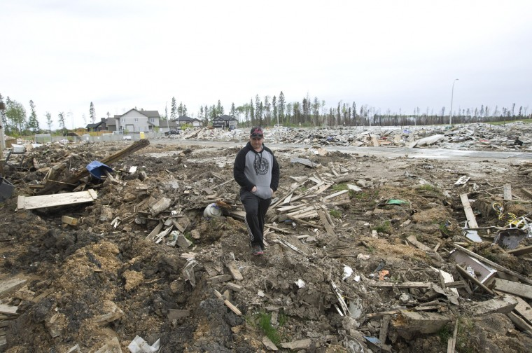 Resident Kenny Gibbons looks through his demolished backyard in the neighborhood of Timberlea, in Fort McMurray, Canada, on Wednesday, June 1, 2016. Residents started to return to the fire-damaged city in northern Alberta on Wednesday, but officials have warned that they should not expect everything to be running normally right away. (Jason Franson/The Canadian Press via AP)
