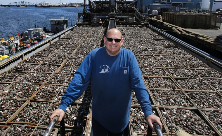 Mike Mohr, captain of the fishing vessel E.S.S. Pursuit, poses while offloading a two-day haul of quahog clams at a dock in New Bedford, Mass. Those clams, which he once caught off the New Jersey shore, have migrated northward or farther out to sea. About 10 years ago, Mohr started commuting six hours each way from his New Jersey home to New Bedford to harvest them. (AP Photo/Charles Krupa)