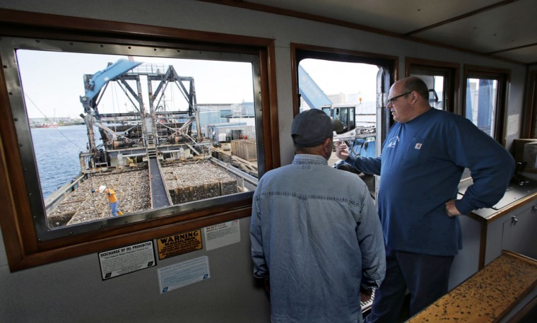 In this Thursday, May 19, 2016 photo, Mike Mohr, right, captain of the fishing vessel E.S.S. Pursuit, talks with his first mate while offloading a two two-day haul of quahog clams at a dock in New Bedford, Mass. Mohr commutes from his home in New Jersey to New Bedford so he and his 28-year-old son Danny can spend 20 days out of 30 aboard his ship to harvest the clams. (AP Photo/Charles Krupa)