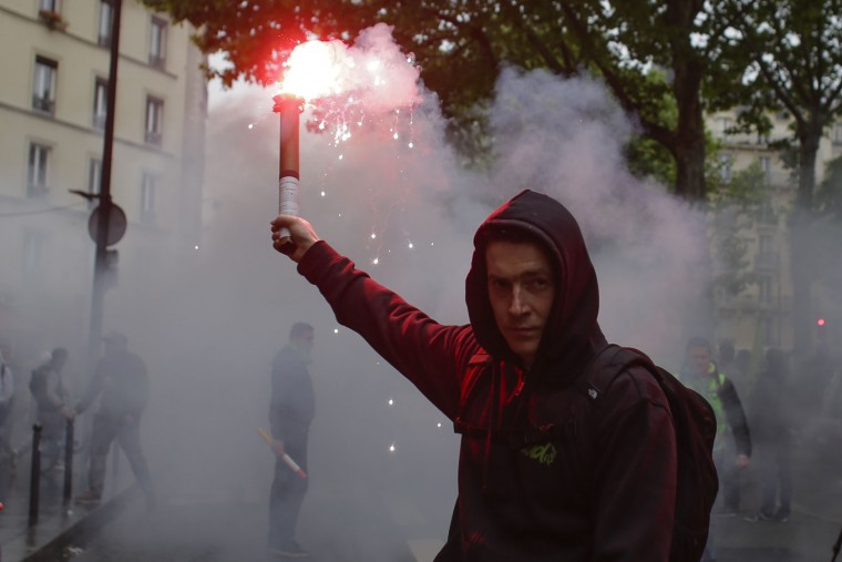 A man holds a flare at a demonstration of labor union members on strike against the French government and labor law reforms in Paris, Thursday, June 2, 2016. Workers are on strike at nearly all of France's nuclear plants and on the national rail service as part of months of protests over changes to labor protections. (AP Photo/Markus Schreiber)