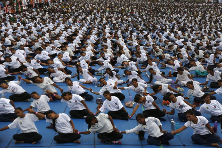 Indians holds each others' hands as they attempt to create a record of longest human yoga chain with more than 8000 participants at an event to celebrate International Yoga Day in Ahmadabad, India, Tuesday, June 21, 2016. Millions of yoga enthusiasts are bending their bodies in complex postures across India as they take part in a mass yoga program to mark the second International Yoga Day. (AP Photo/Ajit Solanki)