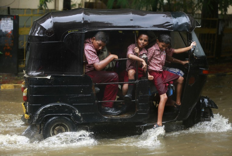 School children ride an auto rickshaw through a flooded street as it rains in Mumbai, India, Tuesday, June 28, 2016 . Monsoon rains, which started off slow in the city, has picked up pace the past few days. India's monsoon season runs from June to September. (AP Photo/Rafiq Maqbool)