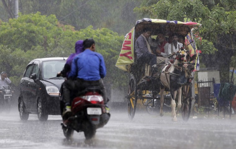 A horse driven cart ferries commuters as it rains in Allahabad, India, Thursday, June 23, 2016. After a couple of years of deficient monsoons, the Indian meteorological department has predicted a wetter than normal monsoon season in 2016. (AP Photo/ Rajesh Kumar Singh)