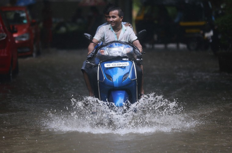 A man rides a scooter through a flooded street in Mumbai, India, Tuesday, June 28, 2016 . Monsoon rains, which started off slow in the city, has picked up pace the past few days. India's monsoon season runs from June to September. (AP Photo/Rafiq Maqbool)