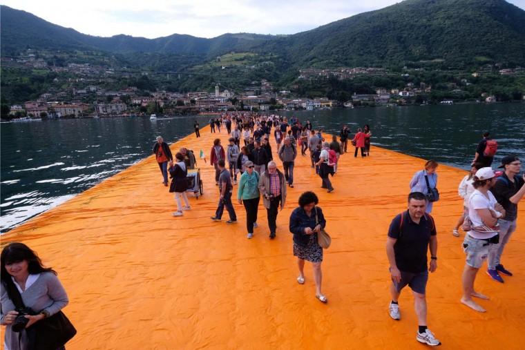People walk on the installation 'The Floating Piers' by Bulgarian-born artist Christo Vladimirov Yavachev known as Christo, on the Lake Iseo, northern Italy, Saturday, June 18, 2016. (Filippo Venezia/Ansa via AP)