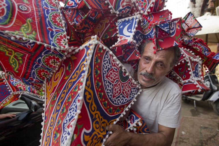 An Egyptian vender carries dozens of modern cloth lanterns marking the holy month of Ramadan at a market in the neighborhood of Sayeda Zeinab, Cairo, Egypt, Friday, June 3, 2016. Devout Muslims throughout the world will begin to celebrate Ramadan next week, the holiest month in the Islamic calendar, refraining from eating, drinking, smoking and sex from sunrise to sunset. (AP Photo/Amr Nabil)