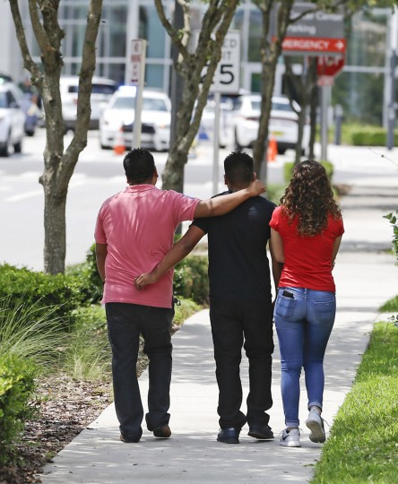 A group of people walk to the emergency room of Orlando Regional Medical Center after a shooting involving multiple fatalities at a nightclub, Sunday, June 12, 2016, in Orlando, Fla. (AP Photo/John Raoux)