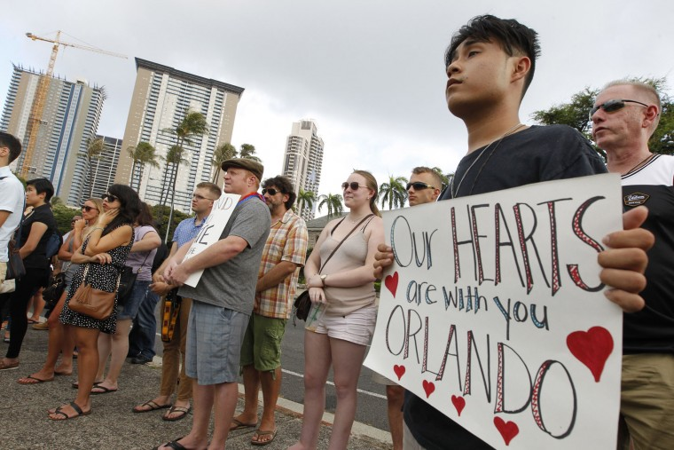 In this Sunday, June 12, 2016 photo, among the several dozen gathered, Isaiah Chong, right, held a sign of sympathy during a vigil on Sunday held at Honolulu Hale to remember the victims of the Orlando, Fla., nightclub mass shooting, in Honolulu. A gunman killed dozens of people in a massacre at a crowded gay nightclub in Orlando on Sunday, making it the deadliest mass shooting in modern U.S. history. (George F. Lee/The Star-Advertiser via AP)