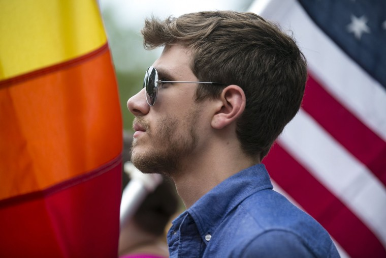 Matthew Derrick holds a rainbow flag during a vigil honoring the Orlando, Fla. mass shooting victims hosted by the Kalamazoo Gay Lesbian Resource Center in Kalamazoo, Mich. on Monday, June 13, 2016. A gunman has killed dozens of people in a massacre at a crowded gay nightclub in Orlando, Fla. on Sunday, making it the deadliest mass shooting in modern U.S. history. (Chelsea Purgahn/Kalamazoo Gazette-MLive Media Group via AP)