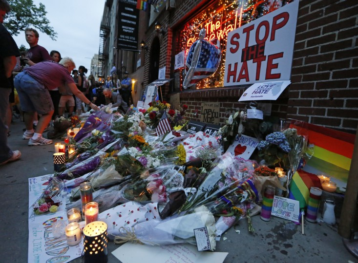 A person lays flowers at a makeshift memorial for the Orlando shooting victims in front of the Stonewall Inn, a historic gay bar, during a vigil for the victims, Monday, June 13, 2016, in New York. State and city officials, LGBT community members, and others gathered as a show of solidarity with the victims and survivors of the Orlando nightclub shootings, the worst mass shooting in modern U.S. history. (AP Photo/Kathy Willens)