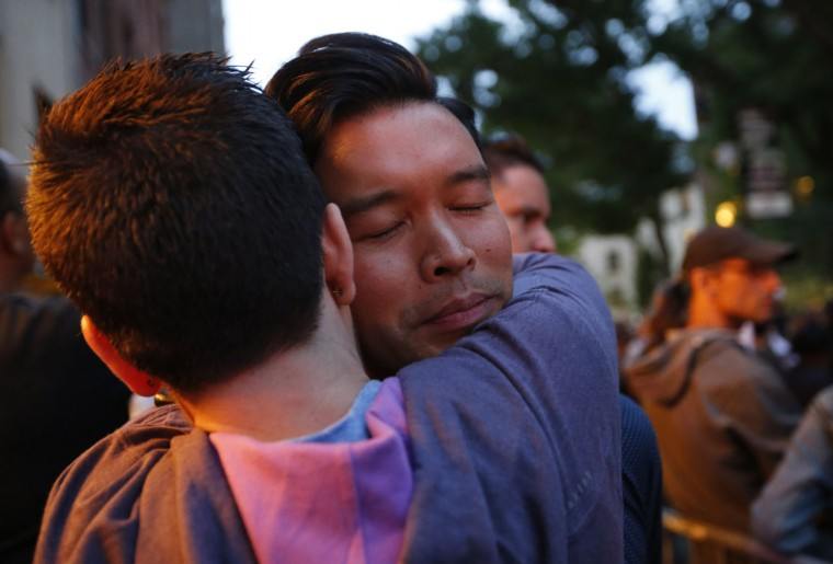 Kalaya'An Mendoza embraces a friend after losing his temper and yelling at people reading victims' names during a vigil and memorial for victims of the Orlando nightclub shootings at the historic Stonewall Inn, a gay bar, Monday, June 13, 2016, in New York. State and city officials, LGBT community members, and others gathered as a show of solidarity with the victims and survivors of the Orlando nightclub shootings, the worst mass shooting in modern U.S. history. (AP Photo/Kathy Willens)