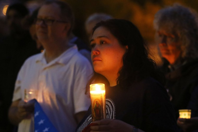 Marina Phelps, center, of Winston, Ore., holds a gay pride flag along with Stephen Phelps, left, during a candlelight vigil in Roseburg, Ore., Monday, June 13, 2016, for the victims of the Orlando nightclub shooting. (Mike Henneke/The News-Review via AP)