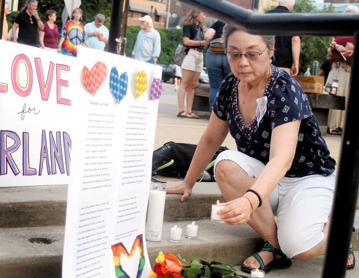 Kathie Shiba lays a candle at the foot of the list of victims of the Orlando mass shooting during a candlelight vigil on the Maryville greenbelt on Monday, June 13, 2016, in Maryville, Tenn. A gunman killed dozens of people in a massacre at a crowded gay nightclub in Orlando on Sunday, making it the deadliest mass shooting in modern U.S. history. (Tom Sherlin/The Daily Times via AP)