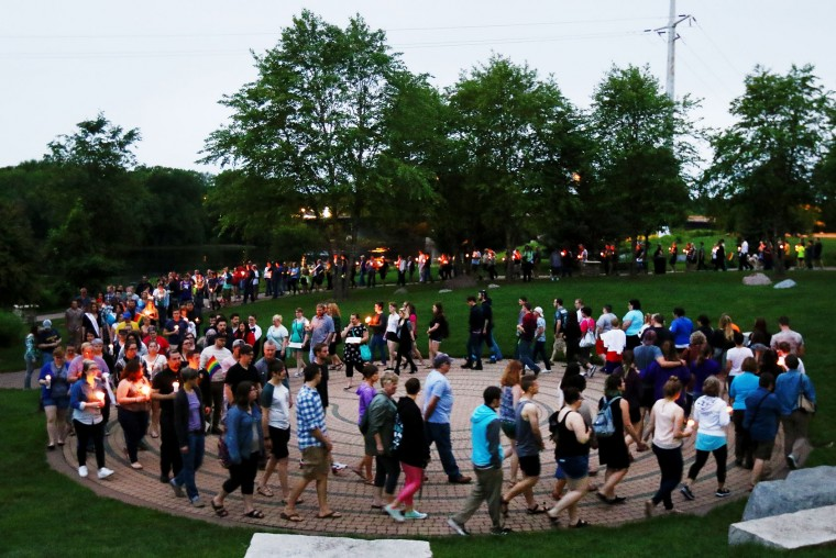 After community members spoke, the candlelight vigil attendees walked from the Phoenix Park Pavilion to the park labyrinth in solidarity with the victims of the Orlando shooting Monday evening, June 13, 2016, in Eau Claire, Wis. A gunman killed dozens of people in a massacre at a crowded gay nightclub in Orlando on Sunday, making it the deadliest mass shooting in modern U.S. history. (Marisa Wojcik/The Eau Claire Leader-Telegram via AP)