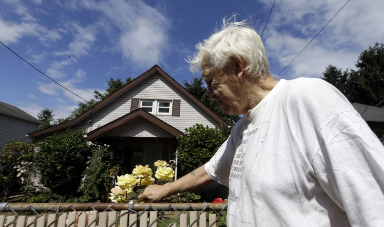 "Bob Wheeler, who has lived in the same house since he was 14 years old, tends to the roses he planted in the front yard for his now-deceased mother at his home in Portland, Ore., Tuesday, June 14, 2016. City officials in this booming Pacific Northwest metropolis have developed a plan to foreclose on so-called ""zombie homes"" for first time in 50 years as Portland grapples with a swelling population and skyrocketing home costs that threaten to lock new homeowners out of the market. (AP Photo/Don Ryan)"