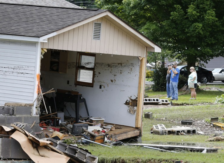 Spectators photograph the remnants of a home as the cleanup begins from severe flooding in White Sulphur Springs, W. Va., Friday, June 24, 2016. A deluge of 9 inches of rain on parts of West Virginia destroyed or damaged more than 100 homes and knocked out power to tens of thousands of homes and businesses. (AP Photo/Steve Helber)