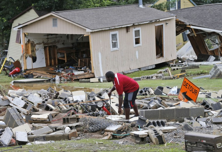 A White Sulphur Springs resident sorts through debris as the cleanup begins from severe flooding in White Sulphur Springs, W. Va., Friday, June 24, 2016. A deluge of 9 inches of rain on parts of West Virginia destroyed or damaged more than 100 homes and knocked out power to tens of thousands of homes and businesses. (AP Photo/Steve Helber)
