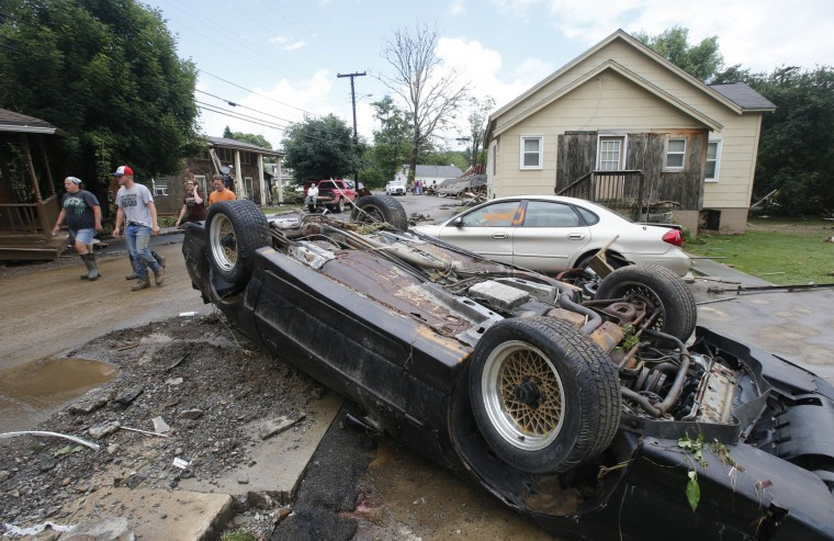 Overturned cars litter the street as residents clean up from severe flooding in White Sulphur Springs, W .Va., Friday, June 24, 2016. A deluge of 9 inches of rain on parts of West Virginia destroyed or damaged more than 100 homes and knocked out power to tens of thousands of homes and businesses. (AP Photo/Steve Helber)