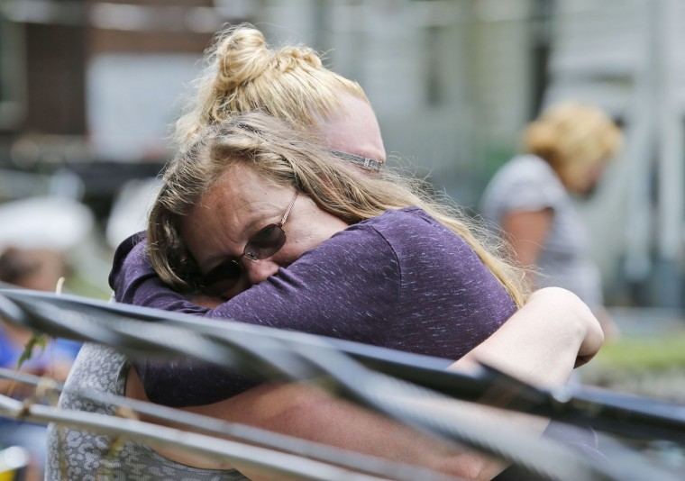 Anna May Watson, right, hugs a relative as they clean up from severe flooding in White Sulphur Springs, W. Va., Friday, June 24, 2016. A deluge of 9 inches of rain on parts of West Virginia destroyed or damaged more than 100 homes and knocked out power to tens of thousands of homes and businesses. (AP Photo/Steve Helber)