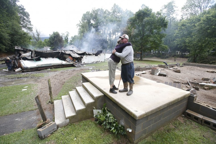 Jimmy Scott gets a hug from Anna May Watson, left, as they clean up from severe flooding in White Sulphur Springs, W. Va., Friday, June 24, 2016. A deluge of 9 inches of rain on parts of West Virginia destroyed or damaged more than 100 homes and knocked out power to tens of thousands of homes and businesses. Scott lost his home to the flood and a fire that consumed his and the homes of several relatives. (AP Photo/Steve Helber)