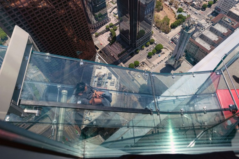 A member of the media rides down a glass slide during a media preview at the U.S. Bank Tower building in downtown Los Angeles on Thursday, June 23, 2016. Starting this weekend, thrill-seekers can ride the Skyslide, a 1,000-ft high slide perched on the outside of the tallest skyscraper west of the Mississippi. (AP Photo/Richard Vogel)