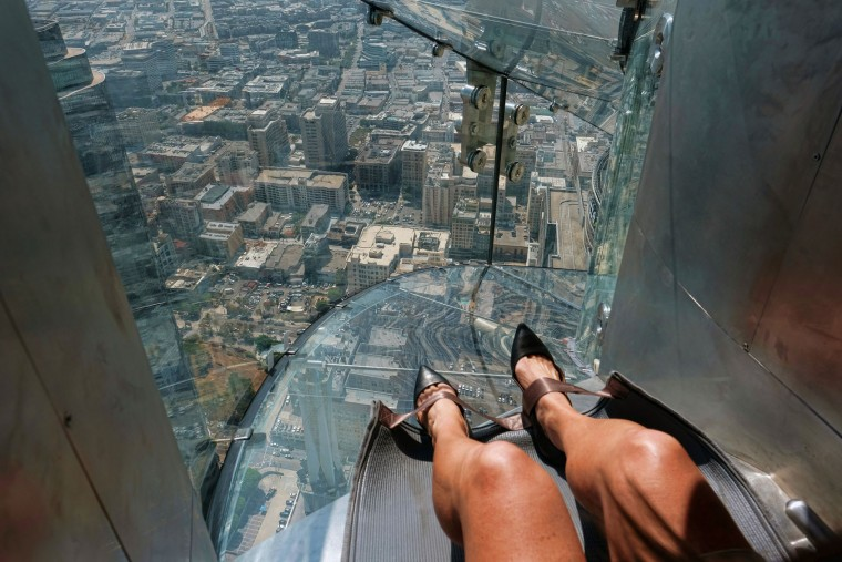A member of the media prepares to take a ride down a glass slide during a media preview day at the U.S. Bank Tower building in downtown Los Angeles on Thursday, June 23, 2016. Starting this weekend, thrill-seekers can begin taking the Skyslide, a 1,000-foot high slide perched outside of the tallest skyscraper west of the Mississippi. (AP Photo/Richard Vogel)