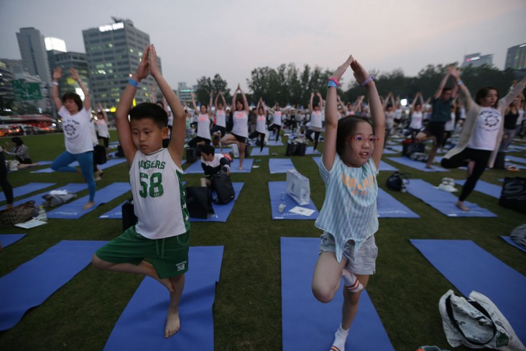 Children perform yoga to mark the International Day of Yoga in downtown Seoul, South Korea, Tuesday, June 21, 2016. Millions of yoga enthusiasts bent and twisted their bodies in complex postures across much of the world on Tuesday to mark the second International Yoga Day. (AP Photo/Ahn Young-joon)