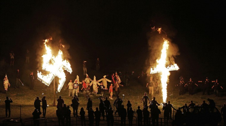 "In this Saturday, April 23, 2016 photo, members of the Ku Klux Klan participate in cross and swastika burnings after a ""white pride"" rally in rural Paulding County near Cedar Town, Ga. The Alabama-based Southern Poverty Law Center, an advocacy group that tracks activity by groups it considers extremist, says there's no evidence the Klan is returning to the strength of its heyday. (AP Photo/Mike Stewart)"