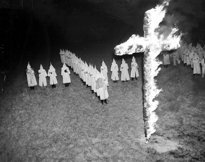 In this Jan. 30, 1939 file photo, members of the Ku Klux Klan, wearing white hoods and robes, watch a burning cross in Tampa, Fla. In 2016, KKK leaflets have shown up in suburban neighborhoods from the Deep South to the Northeast. (AP Photo/File)