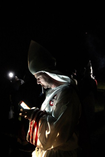 "In this Saturday, April 23, 2016 photo, a member of the Ku Klux Klan uses a mobile device during cross burnings after a ""white pride"" rally in rural Paulding County near Cedar Town, Ga. As the KKK marks 150 years of existence, it is trying to reshape itself for a new era. (AP Photo/John Bazemore)"